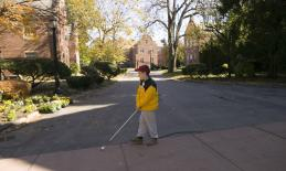 a boy walking with a white cane