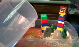 Water being added to container with sand and model buildings