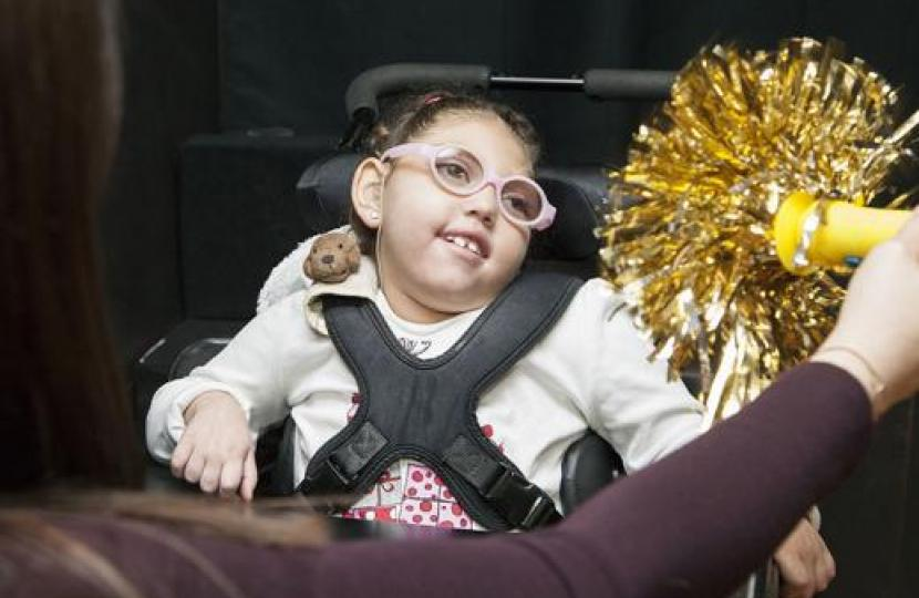 A young girl with glasses is gazing at a shiny pom pom.