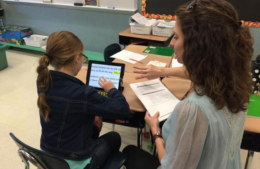 Holding an iPad manual, a TVI demonstrates a 3 finger swipe gesture as a student practices the gesture on her iPad.
