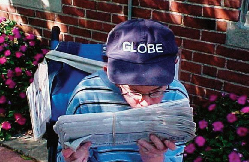 Boy with glasses delivers newspaper