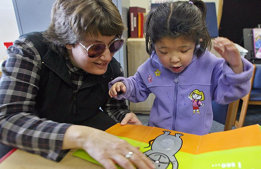 Teacher reading book with young child