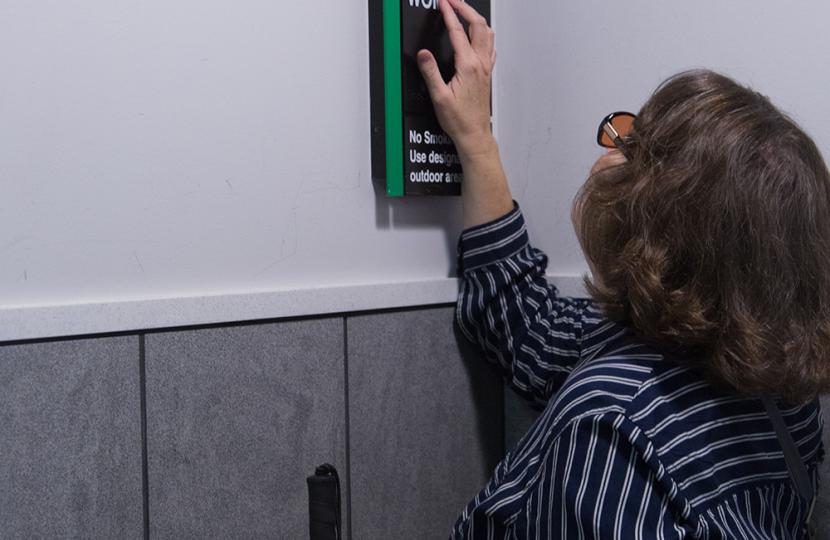 Woman reading woman's bathroom braille sign