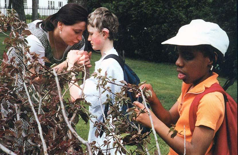A teacher and her students examine leaves on a tree