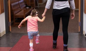 a young girl with a cochlear implant marches confidently down the hall on the hand of her teacher