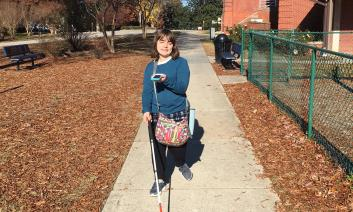 Student using the BlindSquare iPhone app while traveling on a school sidewalk with her long cane.
