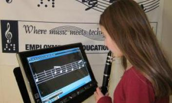 Photo of a girl playing an instrument while looking at a music stand  holding a tablet displaying a measure of musical notes.
