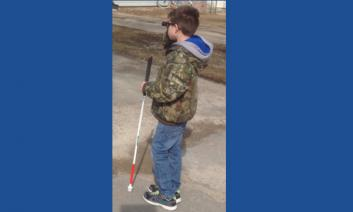 Elementary student standing outside in a jacket looking through a monocular while coding his long cane.