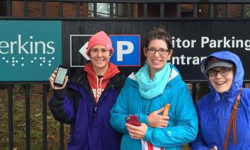 3 smiling O&Ms in rain gear learning to use the BlindSquare navigation app around the Perkins School for the Blind campus.