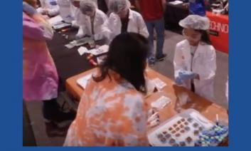 Screenshot from STEM Career Video: Students with lab coats, hair nets and gloves are working with adults  doing lab experiments.