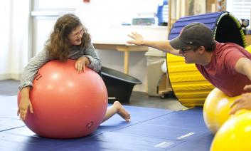 A student with glasses balances a ball in a gym class.