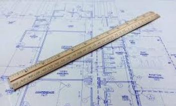The image is of a blueprint with a ruler across it.