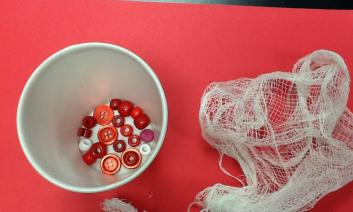 a mixture of beads and buttons in a cup and a piece of gauze