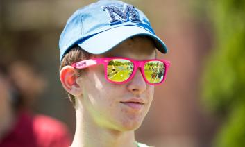 A young man with a cap and sunglasses on.