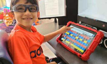 A young student with glasses uses a communication device