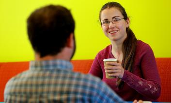a young woman and young man talk while drinking coffee
