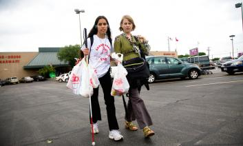 A teacher walking with her student who is carrying several grocery bags and her white cane. The student has earphones on.