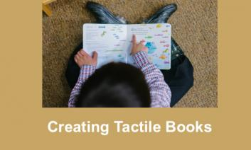 """Overhead image of young boy """"reading"""" and touching a board book."""