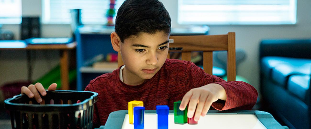 A boy using a lighted table