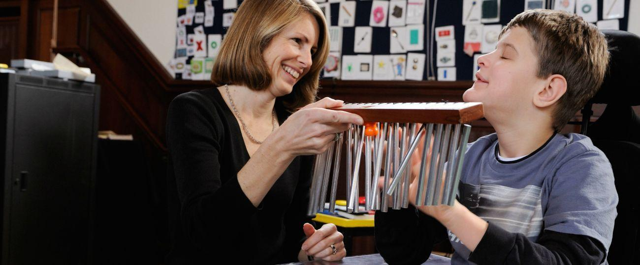 Student plays chimes with teacher.