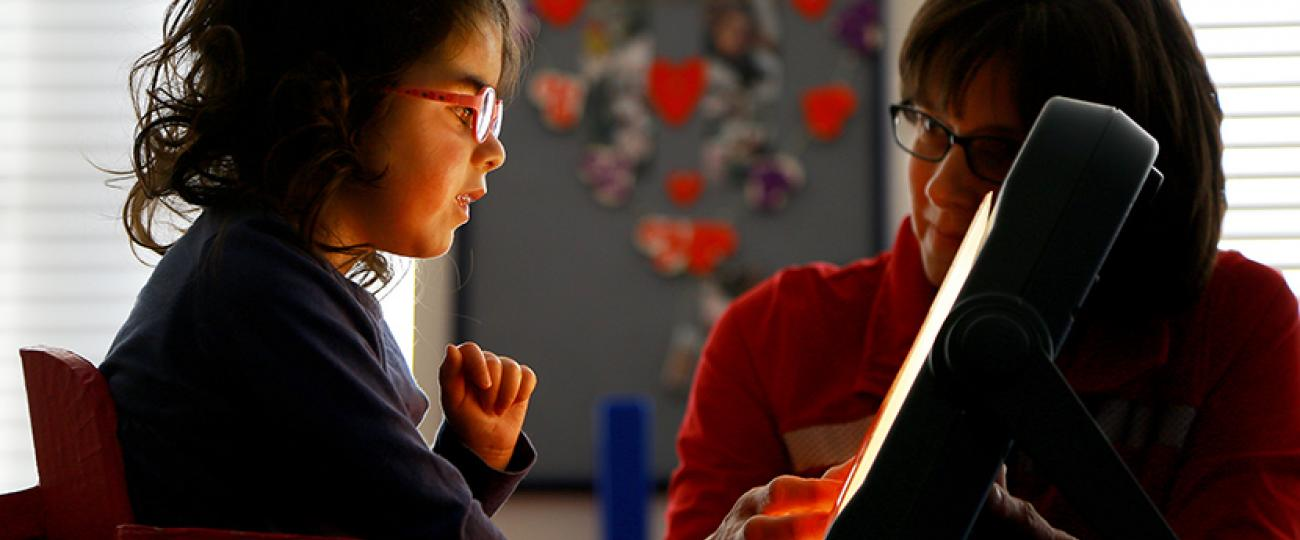 A girl with her teacher using a touch screen.