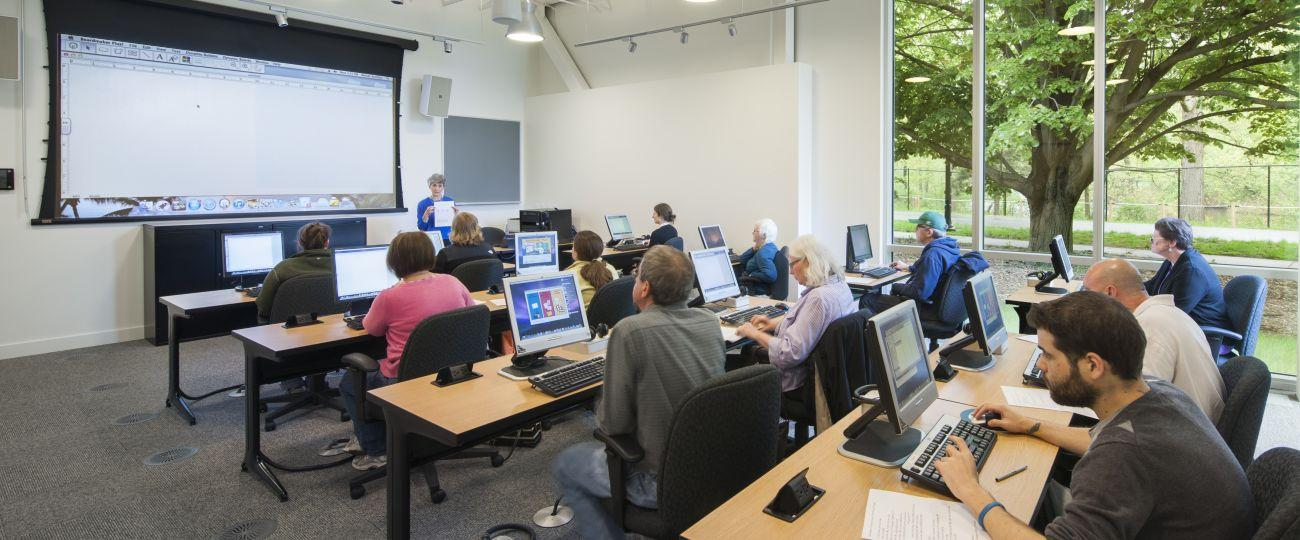 Class of adult learners in technology training room.
