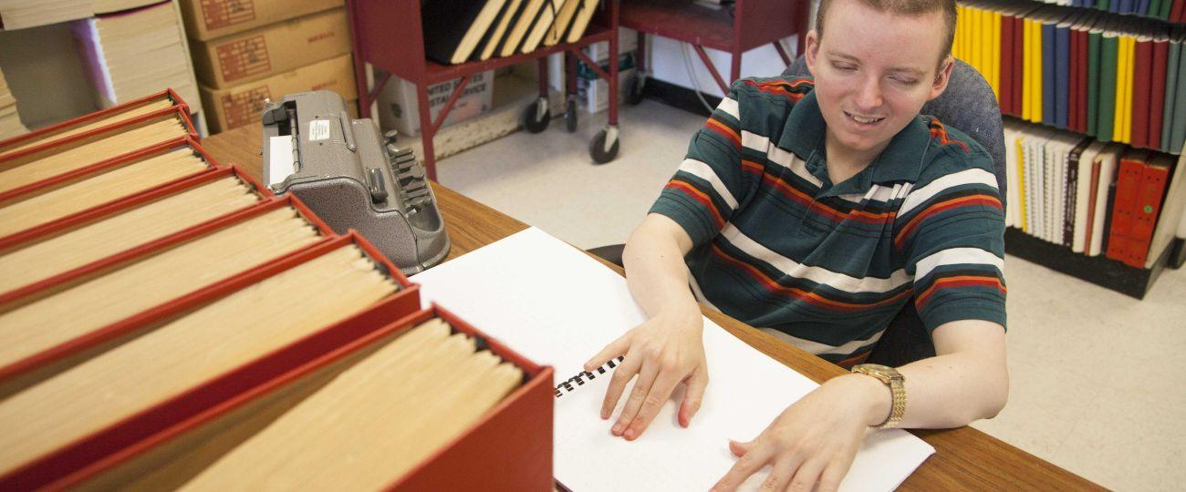 Student reading braille.