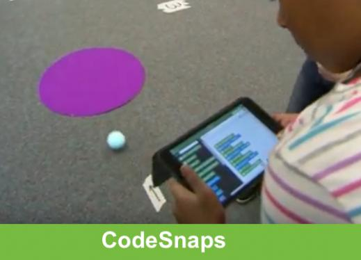 Sphero robot ball navigating the obstacle course with a student holding an iPad running the code.