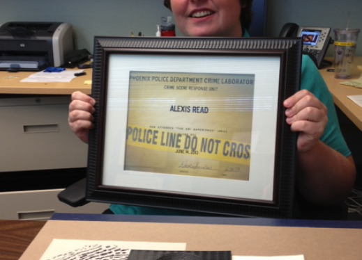 Picture of Alexis holding a framed certificate from the training along with very large finger print samples, etc.