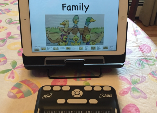 iPad with a screen displaying the title page of the book Quack the Duck's Family and an Orbit Reader 20 braille display on table