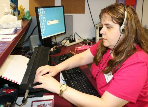 A woman uses a refreshable braille display at an office desk.