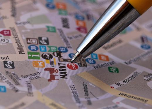 Pen marking a location on a colorful print map.