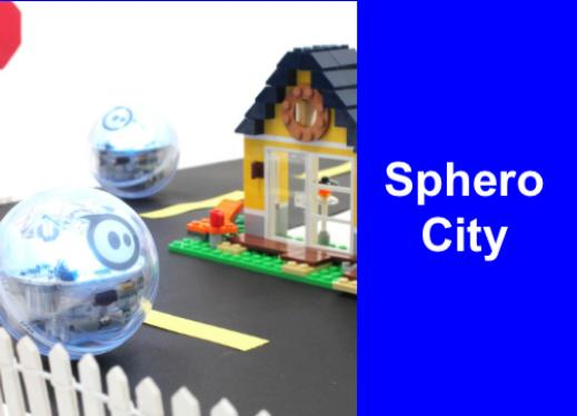 "Sphero ball rolling along street lined with lego house in the background & picket fence with text, ""Sphero City""."