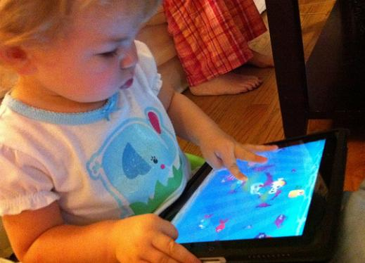 Toddler interacting with an iPad.