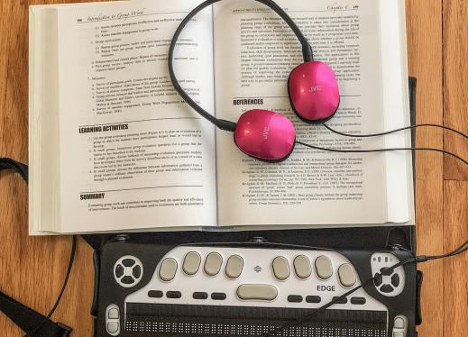 Headphones resting on an open text book above a Braille Edge refreshable braille display,