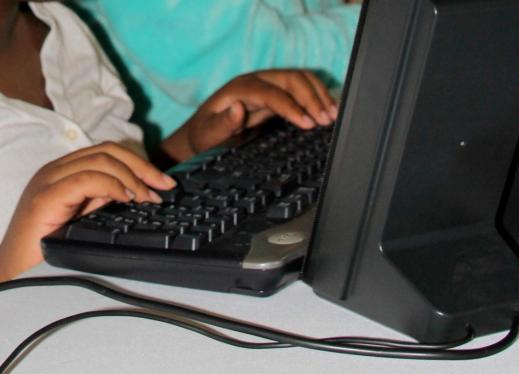 This photo shows a student's hands typing on a keyboard.