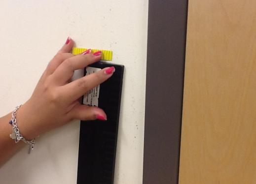 Student uses a tactile marker to measure her height.