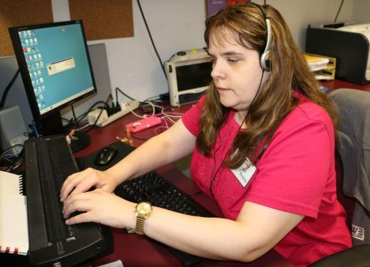 Woman with headphones using refreshable braille display