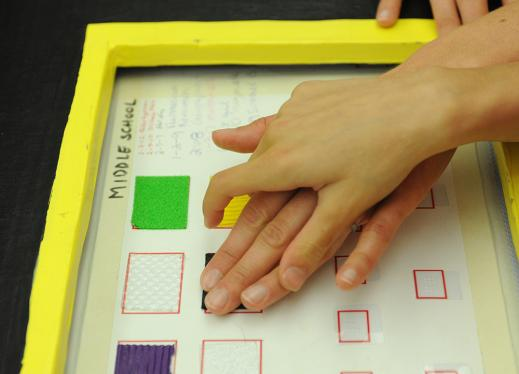 One hand guides another hand over a tactile graphic.