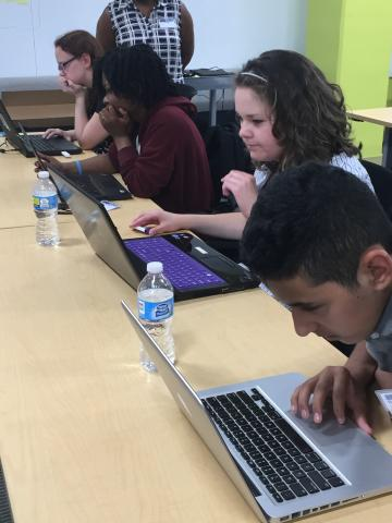 Four high school students in a classroom working individually on their laptops.