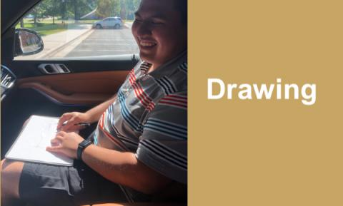 Photo of Victor sitting in a car drawing a campus map using the Sensational BlackBoard tactile drawing tool.