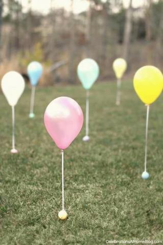 Yard full of colorful balloons attached to Easter eggs.