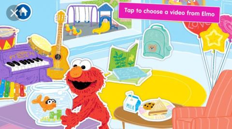 Screenshot of A Busy Day for Elmo app; Elmo is holding a fish tank in a room with a piano chair, table with lunch items on it,