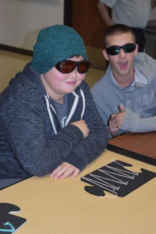 Two high school students smiling and wearing sunglasses with a large puzzle piece with a wavy line in front of them