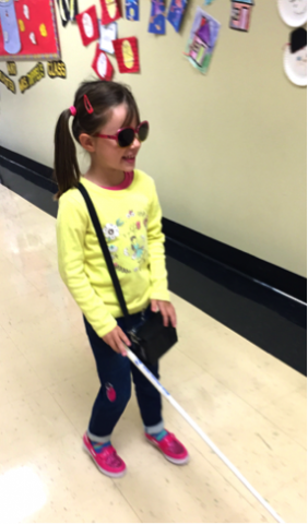 Layla walking down a school hallway with her long cane and her braille display in it's purse-like case over her shoulder.