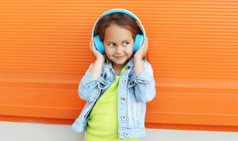 Smiling early elementary-age girl with her hands holding bright blue headphones over her ears.