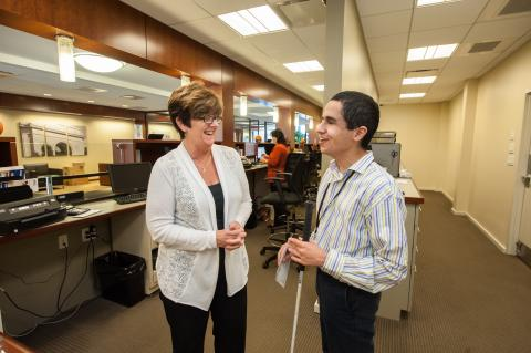 Transition-age youth who is blind meeting with employer in work setting