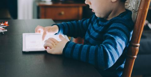 Toddler sitting at a kitchen table with his finger on a glowing iPad screen.