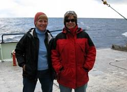 Kate Fraser and Amy Bower stand on the deck of ship with the open ocean in the background