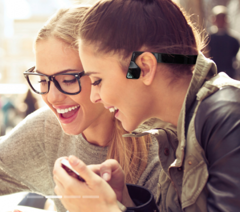 Two girls in class wearing Airshokz and holding a phone.